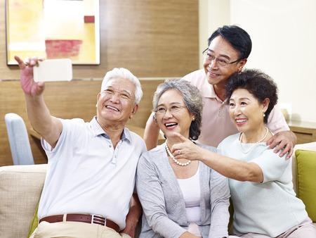 Deux couples seniors prenant un selfie sur le divan chez vous