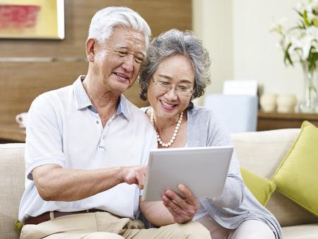 上級アジア夫婦の自宅でタブレット コンピューターを共有
