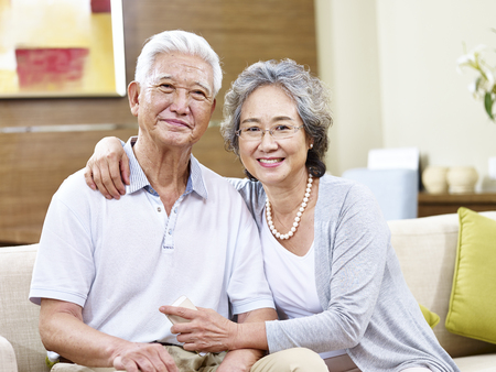 senior asian couple sitting on couch at home looking at camera smiling Stock Photo