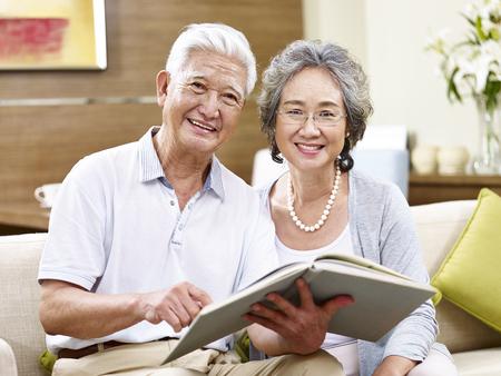 vejez feliz: alto par asiático sentado en el sofá con un libro mirando a la cámara sonriendo