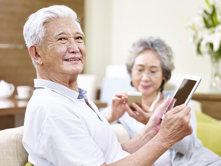 上級アジアのカップルの上に座ってソファのタブレット コンピューターと携帯電話を使用して現代の技術を楽しんで
