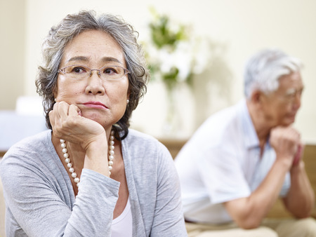 senior asian couple sitting on couch at home, angry at each other