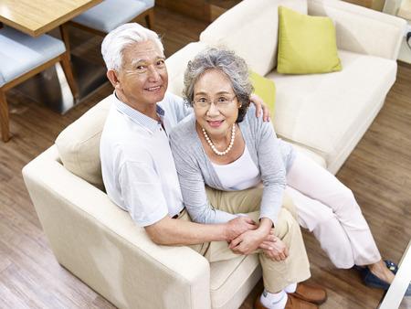 parejas enamoradas: amantes de la pareja asiática de alto sentado en el sofá en casa, de gran ángulo