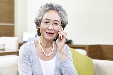 Senior asiatische Frau auf Mobiltelefon spricht, scheint enttäuscht zu sein, verärgert und unglücklich Standard-Bild