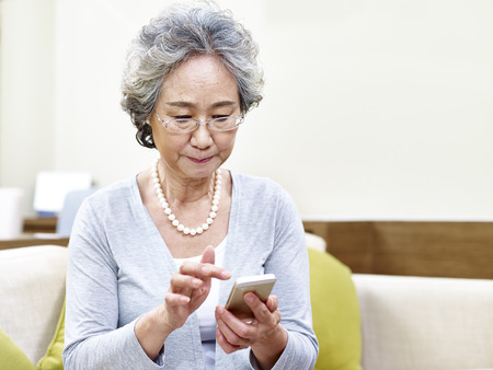 senior asian woman using mobile phone with serious facial expression