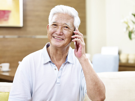 80s adult: senior asian man calling using cellphone, looking at camera smiling Stock Photo
