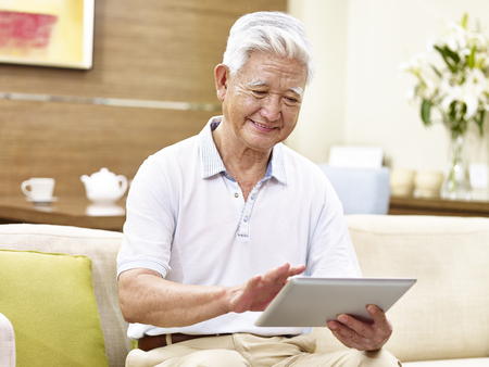 active senior asian man sitting on couch using tablet computer, relaxed, smiling Stock Photo