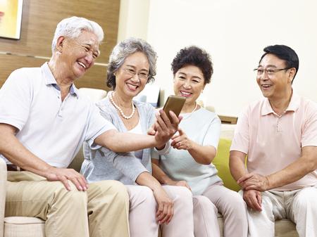 two senior asian couples having fun taking a selfie using cellphone