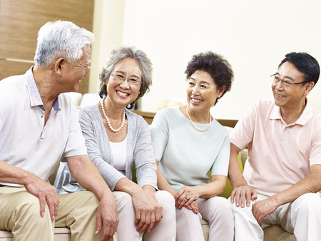 two happy and active senior asian couples sitting on couch chatting smiling