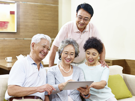 two active senior asian couples looking at tablet computer, happy and smiling