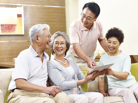 two active senior asian couples looking at tablet computer, happy and laughing