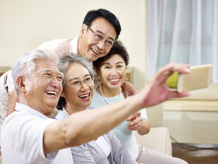 Twee actieve senior Aziatische koppels nemen een selfie met behulp van mobiele telefoon, blij en lachend Stockfoto
