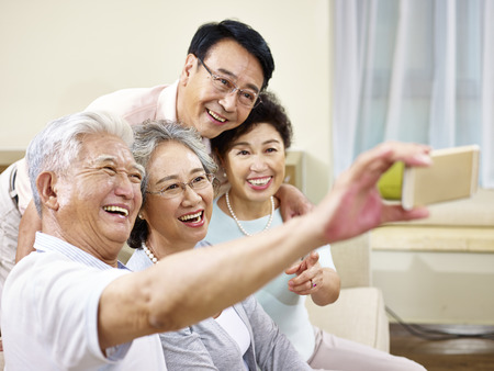 two active senior asian couples taking a selfie using mobile phone, happy and smiling