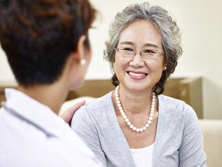 senior asian woman having a pleasant conversation with her family doctor, happy and smiling