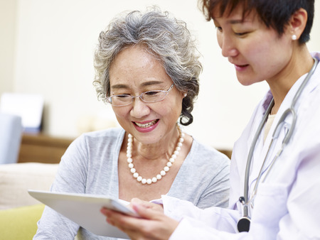 senior asian woman and family doctor having a discussing using tablet computer