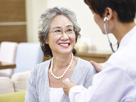 family doctor checking smiling senior asian woman using stethoscope