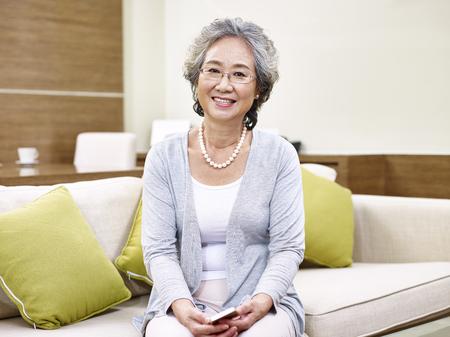笑みを浮かべてカメラを見て、自宅でソファに座っている年配のアジア女性