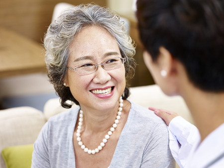 comforted: happy smiling senior asian woman talking and being comforted by a female doctor.