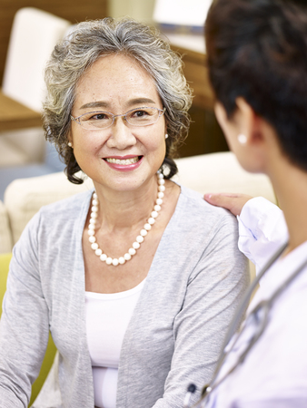 happy smiling senior asian woman talking and being comforted by a female doctor.