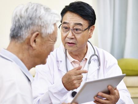 고위 환자에게 건강 상태를 설명하는 아시아 의사