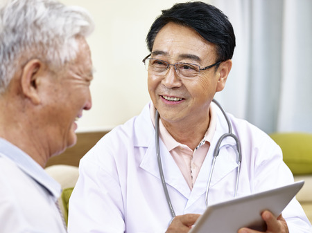 asian doctor talking to a senior patient, happy and smiling Stock Photo
