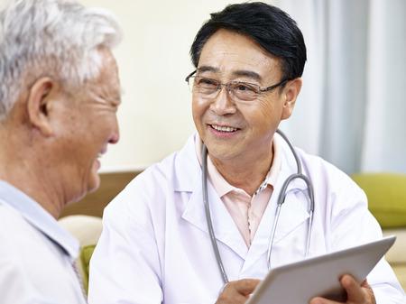 Asiatischen Arzt im Gespräch mit einem älteren Patienten, glücklich und lächelnd