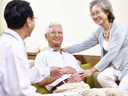 paciente asiático mayor siendo atendido por su esposa y un médico de familia