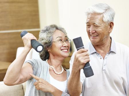 幸せな上級アジア女の夫に彼女の筋肉を示すダンベルを保持