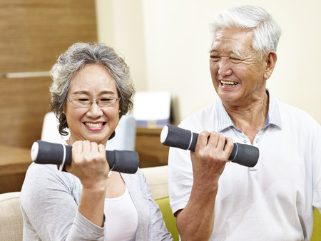joyous: happy senior couple exercising using dumbbells, happy and smiling