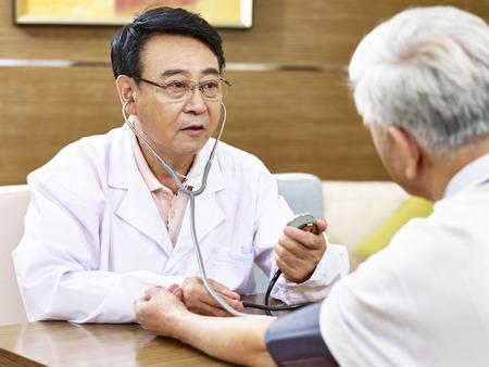 asiático médico medir la presión arterial de un paciente de alto nivel utilizando esfigmomanómetro