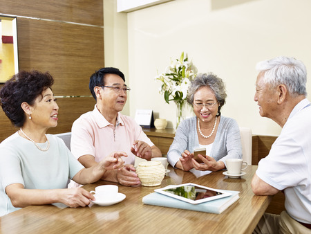 two senior asian couple sitting around the table and chatting