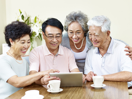 two senior asian couple looking at a tablet Banque d'images
