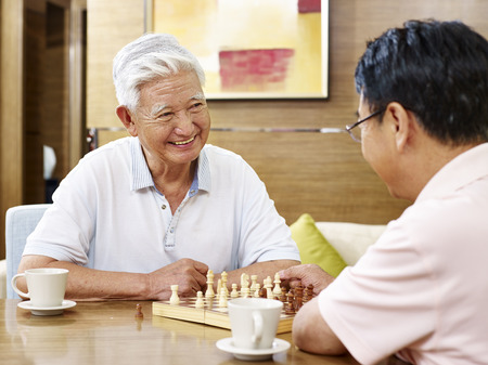 two asian men playing chess game at home