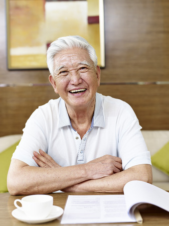 senior asian man reading a book or document in study room Banco de Imagens