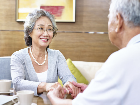 loving senior asian couple drinking coffee and chatting.