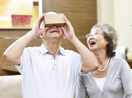 senior asian couple experiencing new technology by trying a vr device