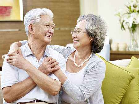 pareja de asiáticos que quieren mirando el uno al otro sonriendo con reconocimiento
