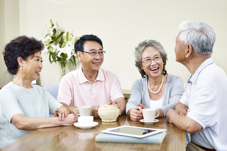 good time: four senior asian people gathering at home having a good time. Stock Photo