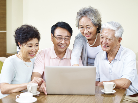 80s adult: four senior asian people gathering at home using laptop computer together.