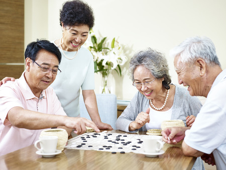 two senior asian men playing Weiqi (or game of go) at home with their wives watching. Stock Photo