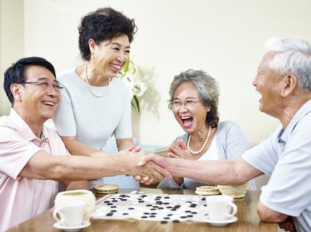 hogere Aziatische mensen die handen schudden op het einde van een weiqi spel.