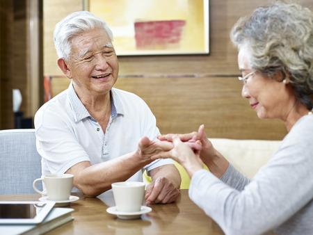 上級アジアの女性は、一緒にコーヒーを持ちながら彼女の夫の手相を読み取ろうとしています。