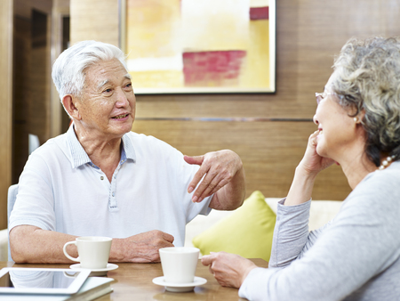 loving senior asian couple sitting at table having coffee and a heated discussion. Stock Photo