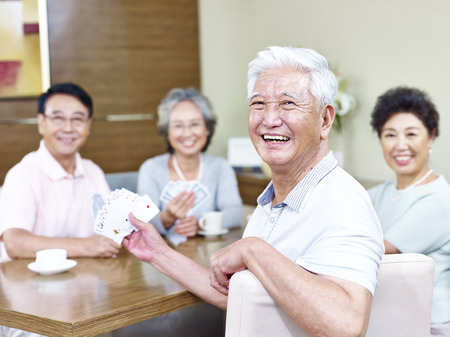 adulto mayor feliz: senior asian man looking at camera smiling while playing cards with friends.