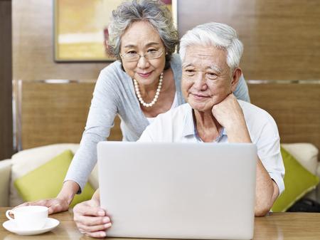 愛するシニアのアジアのカップルは一緒にラップトップ コンピューターを使用して。