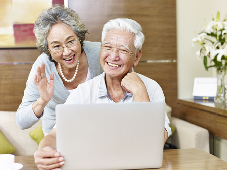 joyous: senior asian couple saying hello during a video chatting.