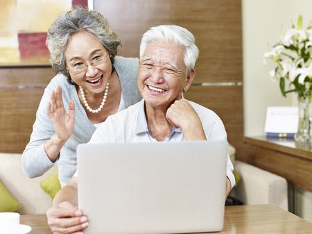 Senior Aziatisch paar zegt hallo tijdens een video chatten. Stockfoto