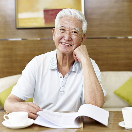 senior asian man reading a book or document in study room Stock Photo