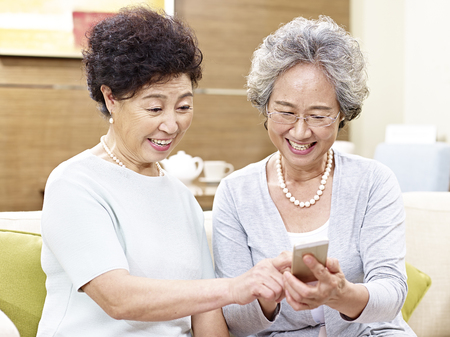 two senior asian women sitting on couch looking at cellphone, happy and smiling