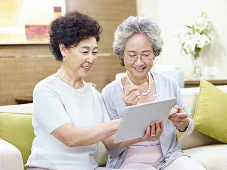 two senior asian women sitting on couch using tablet computer, happy and smiling
